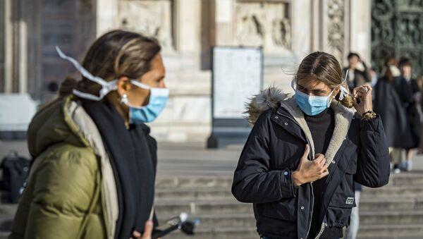 Девушки в масках на одной из улиц Милана - Sputnik Абхазия