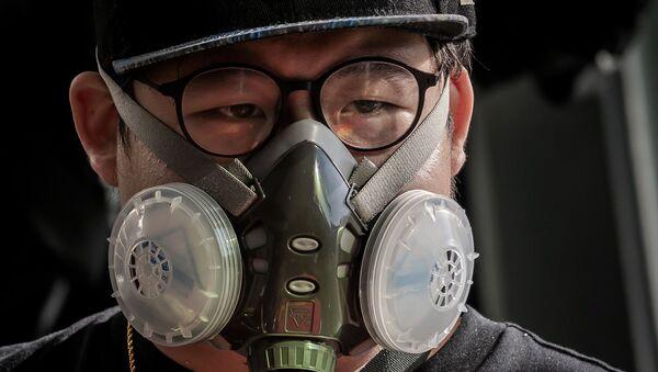 Человек, носящий маску в качестве профилактического средства против коронавируса COVID-19, стоит на эскалаторе возле торгового центра в Пекине 11 марта 2020 года. - Китай сообщил об увеличении числа случаев завоза коронавируса 11 марта, вызвав опасения, что инфекции из-за рубежа может подорвать прогресс в прекращении распространения вируса. - Sputnik Аҧсны
