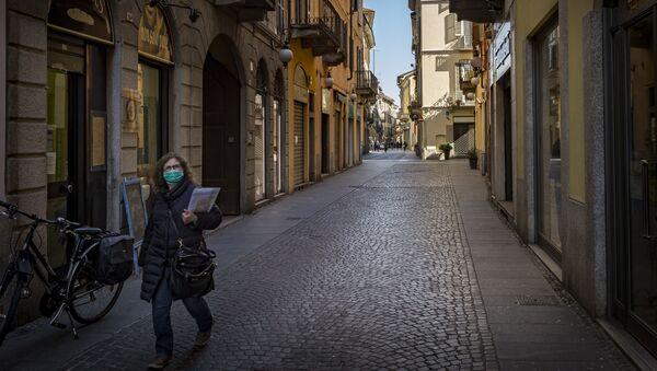 Женщина в маске но одной из улиц Новары, Италия - Sputnik Аҧсны