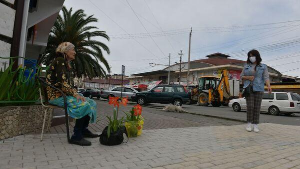 Пожилая женщина продает цветы на улице - Sputnik Абхазия