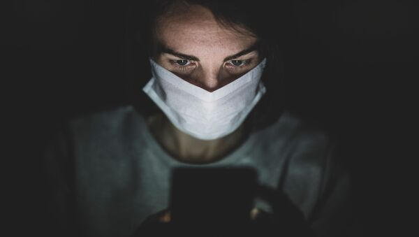 Человек в маске за телефоном - Sputnik Абхазия