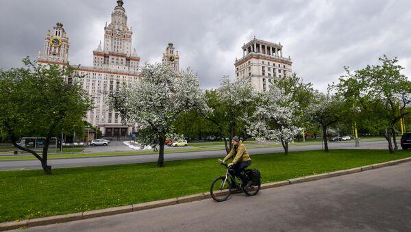 Велосипедист на фоне цветущих деревьев у здания МГУ в Москве - Sputnik Аҧсны