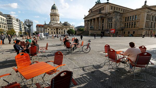 Люди наслаждаются погодой в кафе на площади Жандарменмаркт в Берлине, соблюдая принцип социальной дистанции - Sputnik Аҧсны