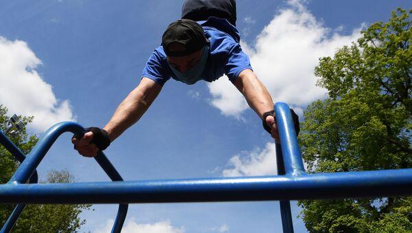 Молодой человек во время выполнения физических упражнений в парке ДК Химиков в Казани - Sputnik Абхазия