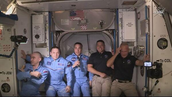 На этом снимке видеокадра НАСА изображены астронавты НАСА SpaceX Crew Dragon Дуглас Херли (R) и Роберт Бенкен (2ndR), прибывающие после открытия люка на Международной космической станции, позирующего вместе с другими астронавтами 31 мая 2020 года. - Американские астронавты на экипаже SpaceX Капсула Дракона заканчивала процедуру окончательного закрытия перед входом в Международную космическую станцию после открытия люка между двумя судами. Люк открылся в 13:02 по восточному времени (1702 по Гринвичу), когда Боб Бенкен и Даг Херли были готовы перейти на станцию, первые американские астронавты, прибывшие на американском космическом корабле за девять лет. - Sputnik Аҧсны