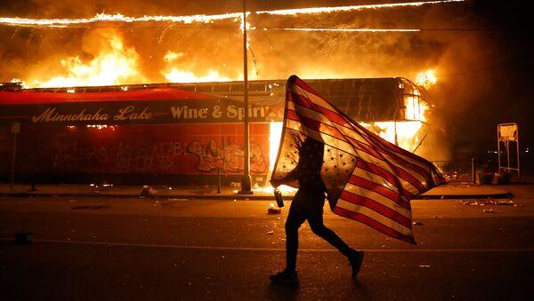 Протестующий с перевернутым флагом США во время демонстрации в связи со смертью Джорджа Флойда, убитого полицейским (28 мая 2020). Миннеаполис - Sputnik Абхазия