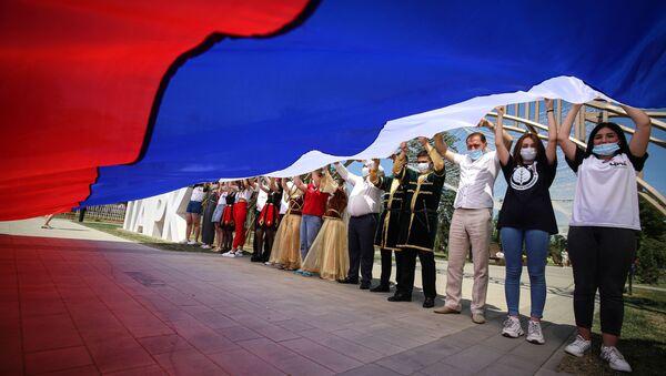Участники празднований Дня России держат российский флаг в парке Дружбы города Георгиевска Ставропольского края - Sputnik Абхазия