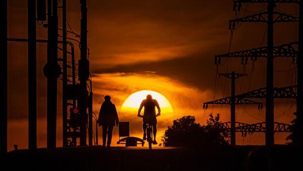 Мужчина едет на велосипеде по одной из улиц в Москве на фоне заката - Sputnik Абхазия