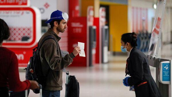 Пассажир предъявляет свой паспорт сотруднику в аэропорту Гатвик, Великобритания - Sputnik Аҧсны